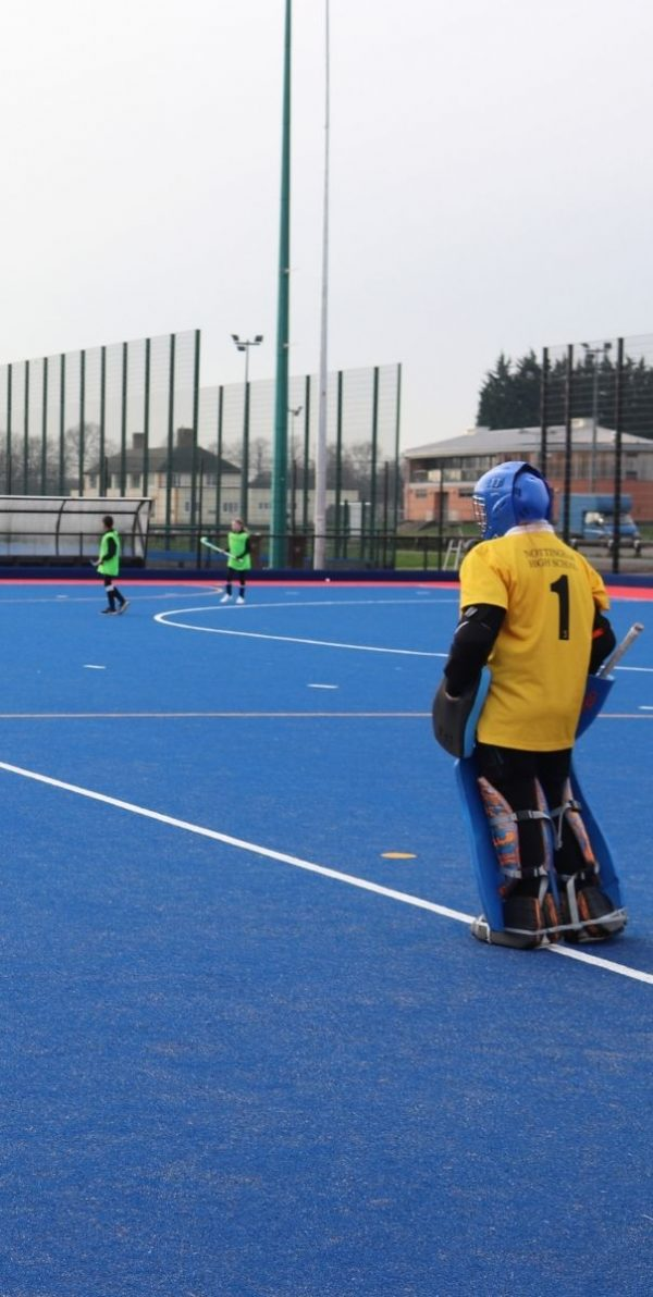Hockey goalkeeper in yellow jersey looking out onto a blue hockey pitch