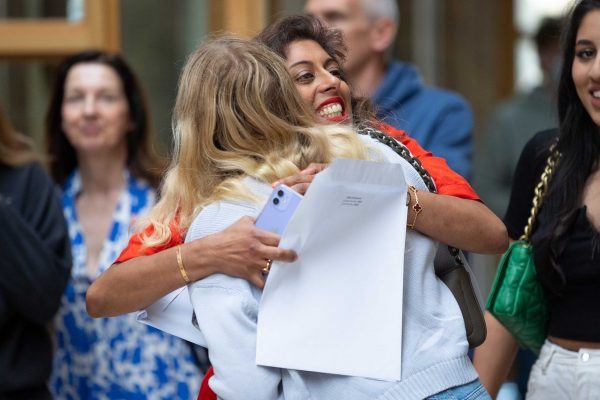 Women is red hugging girl with blonde hair