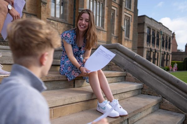 Girl in blue dress sat on stairs showing exam results to friends