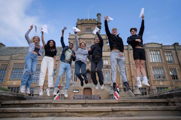 Girls and Boys jumping in the air with exam results